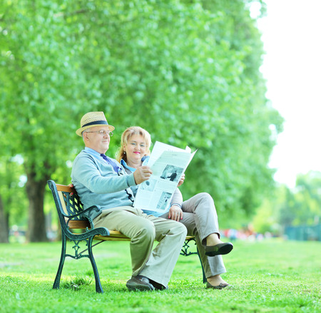 Mature man and woman reading the news outdoors shot with tilt and shift lens photo
