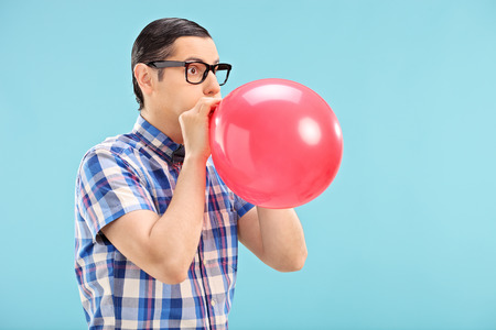 Man with glasses blowing up a balloon on blue background photo