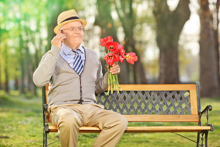 Senior talking on phone and holding red tulips seated on a bench in park photo
