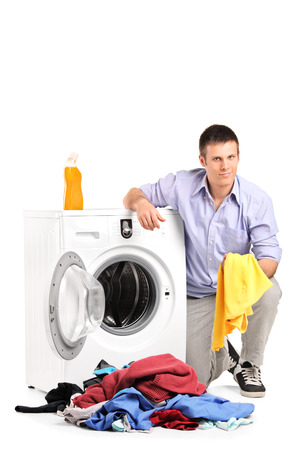Young man emptying a washing machine isolated on white background photo