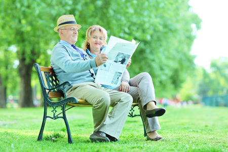 Happy mature couple reading a newspaper outdoors photo