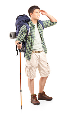 adventurer: Full length portrait of a young hiker looking in the distance isolated on white background