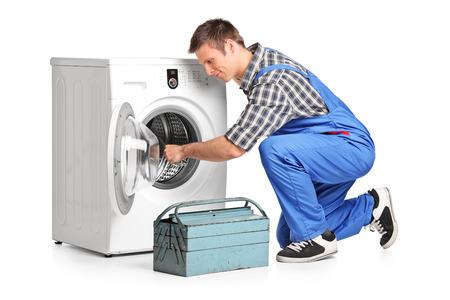 washing machine: Young plumber fixing a washing machine isolated on white background