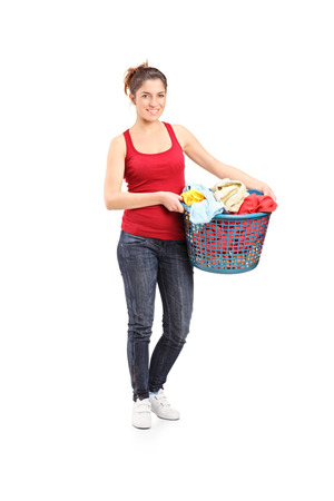 laundry basket: Full length portrait of a young woman holding a laundry basket isolated on white background Stock Photo