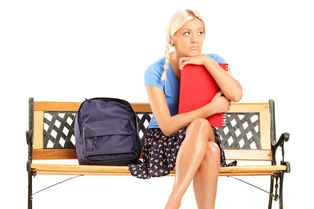 Worried female student sitting on a bench isolated on white background photo