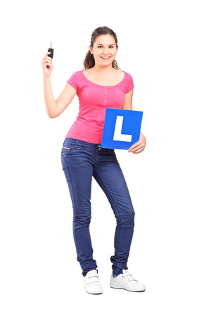 Full length portrait of a girl holding an l sign and a car key isolated on white background photo