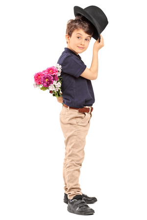 Profile shot of a cute little boy holding flowers behind his back isolated on white background photo