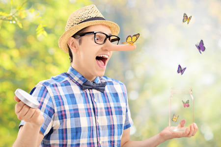 releasing: Excited man releases butterflies from jar outdoors with the focus on the one standing on his nose Stock Photo