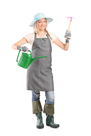 mattock: Full length portrait of a female gardener holding mattock and watering can isolated