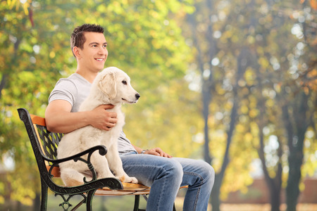 man dog: Man sitting on bench with a young dog
