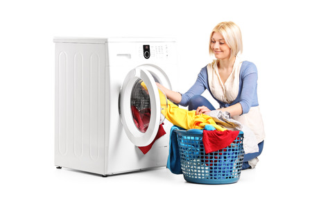 doing laundry: Woman emptying a washing machine isolated on white