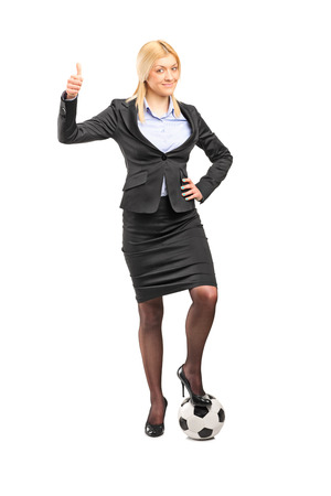 Full length portrait of a businesswoman standing on a football and giving thumb up isolated  photo