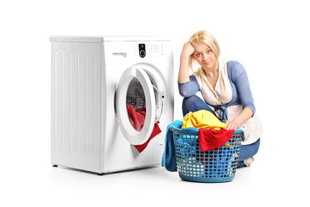 doing laundry: Bored woman sitting by a washing machine and doing laundry isolated Stock Photo