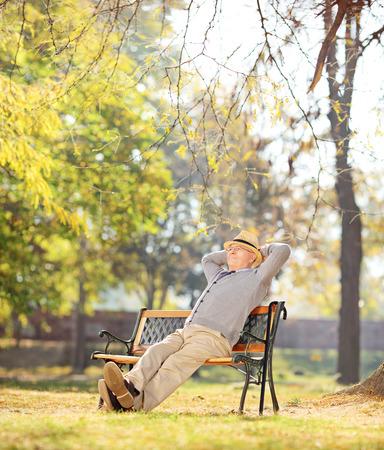 vestidos antiguos: Pensionista relajado sentado en un banco en el parque de tiro con inclinaci�n y desplazamiento de la lente