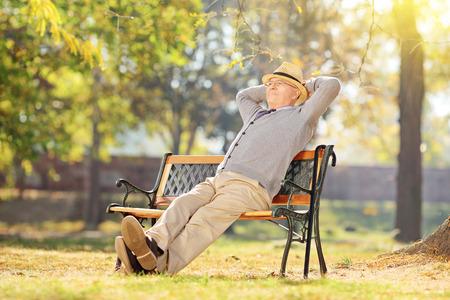 Älterer Mann, der im Park sich entspannt an einem sonnigen Tag auf einer Holzbank sitzt