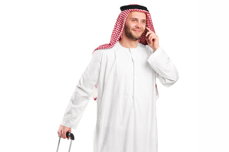 sheik: Arabic sheik talking on phone and carrying a luggage isolated on white background Stock Photo