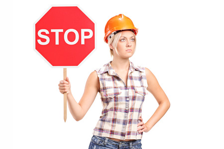 woman stop: Female construction worker holding a stop sign isolated on white background Stock Photo