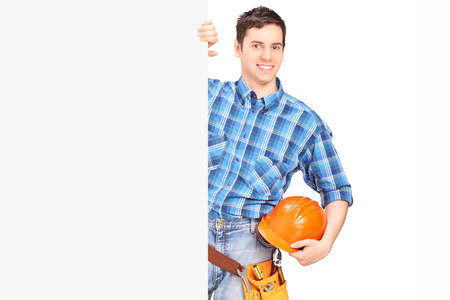 Male construction worker standing behind blank panel isolated against white background photo