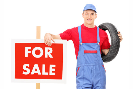 Male mechanic standing by a for sale sign isolated on white background photo
