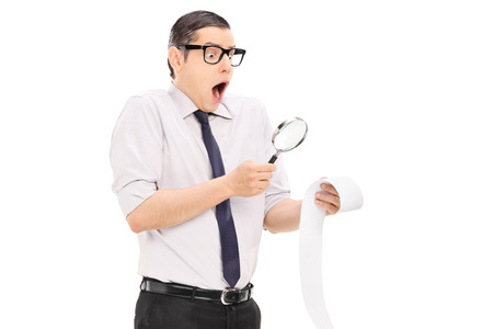 disbelief: Man with magnifier looking at a bill in disbelief isolated on white background Stock Photo