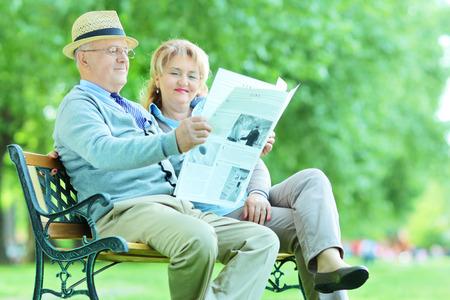 oude krant: Oudere man en vrouw het lezen van het nieuws buiten