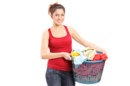 Young woman holding a laundry basket isolated on white background photo