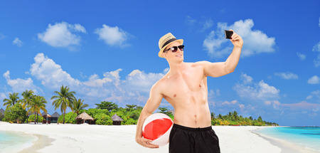 Panoramic view of a handsome man taking a selfie on a tropical beach at Maldives islands photo