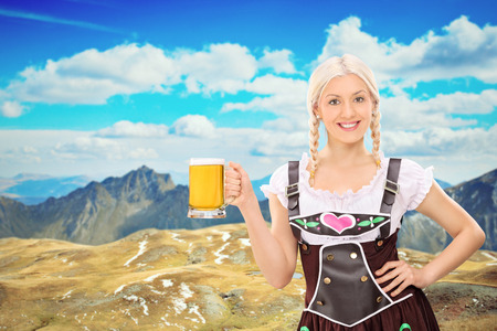 Beautiful Bavarian woman holding a pint of beer somewhere high in the mountains photo