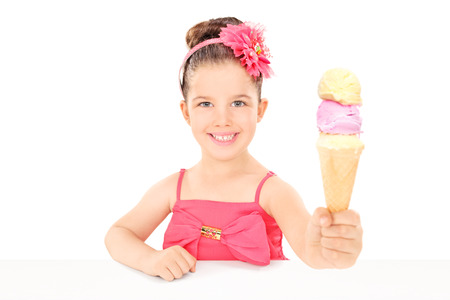 Cute little girl sharing an ice cream seated at table isolated on white background photo