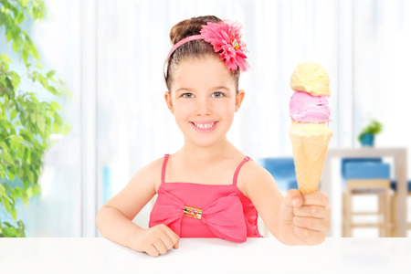 Girl holding ice cream sitting in the living room at home photo