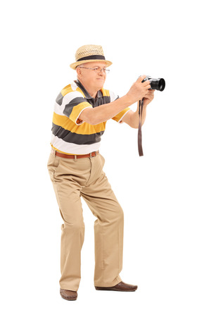 Full length portrait of a mature man taking a picture with a camera isolated on white background photo