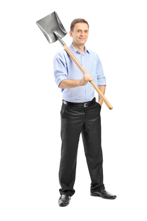 Full length portrait of a young man posing with a shovel over his shoulder isolated photo