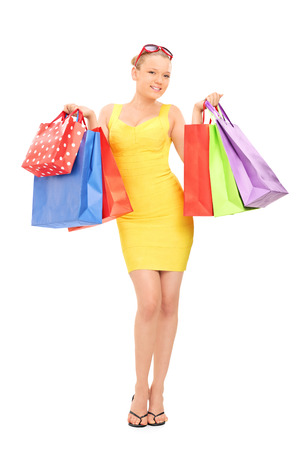 Full length portraot of a woman holding a bunch of shopping bags isolated  photo