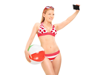 Woman holding a beach ball and taking selfie isolated on white  photo
