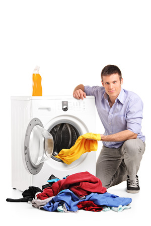 Young man doing laundry isolated on white  photo