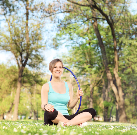 Smiling woman holding a hula hoop seated in meadow shot with tilt and shift lens photo