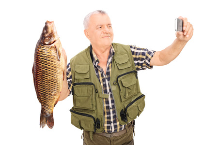 Mature fisherman holding a fish and taking selfie isolated on white background photo