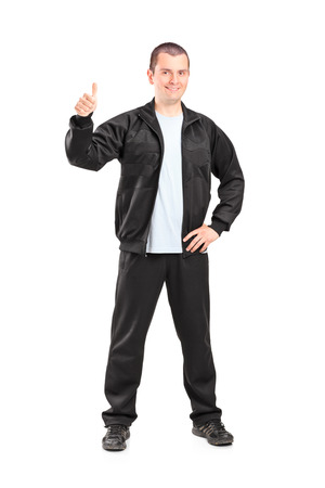 posing  agree: Full length portrait of a young man in black tracksuit giving a thumb up isolated on white background Stock Photo
