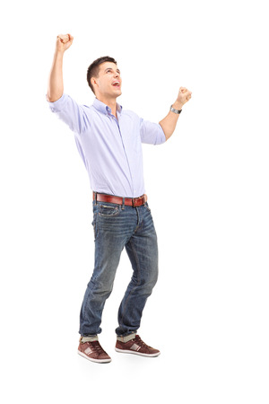 raising hands: Full length portrait of an overjoyed young man isolated on white background
