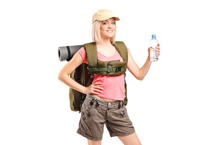 A woman hiker with backpack holding a bottle of water isolated on white background photo