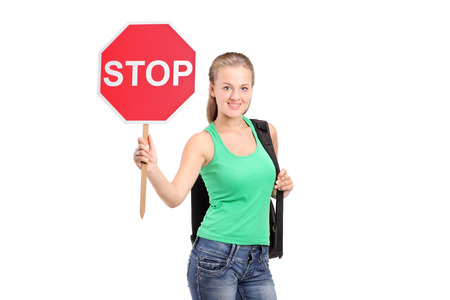 A young woman holding a traffic sign stop isolated on white background photo