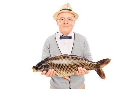 Senior gentleman holding a freshwater fish isolated on white background photo