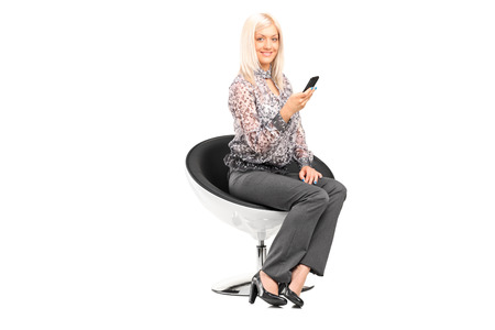 Woman holding a cell phone seated in modern chair isolated on white background photo