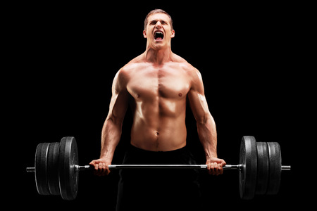 Young man lifting a heavy weight isolated on black background photo