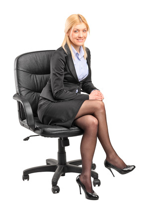 Blond businesswoman sitting in an office chair isolated on white background photo