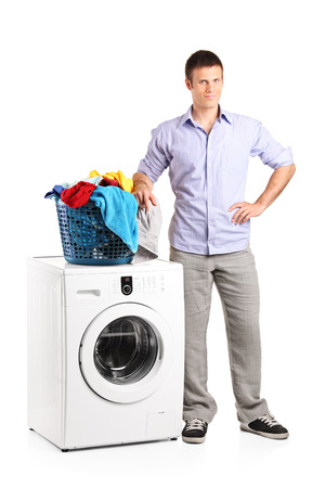 Full length portrait of a guy standing by a washing machine with a laundry basket on it isolated on white background photo