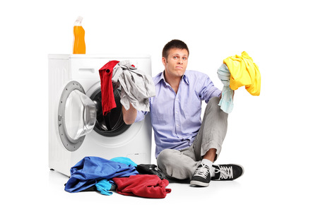 doing laundry: Confused young man doing laundry seated by a washing machine isolated on white background Stock Photo