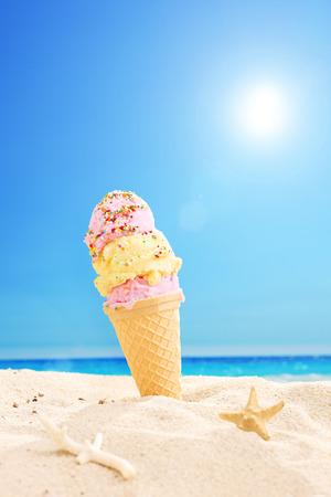 背景の空と太陽が降り注ぐ熱帯のビーチの砂で立ち往生アイス クリーム