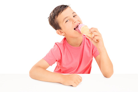 Joyful little boy eating an ice cream seated at a table isolated on white background photo