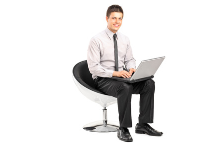 man in chair: Man working on laptop seated in a modern chair isolated on white background